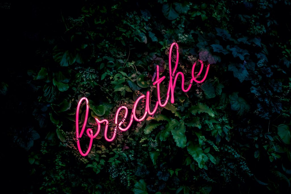 """Pink neon sign that says """"breathe"""""""