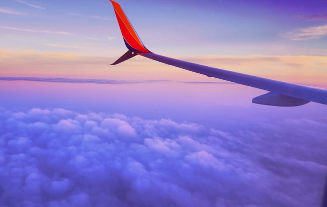 A plane wing above clouds in the sky