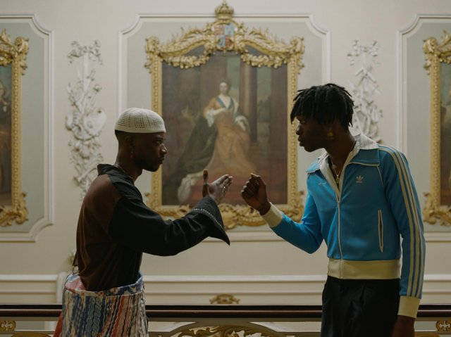 Two black people greeting each other in a museum.